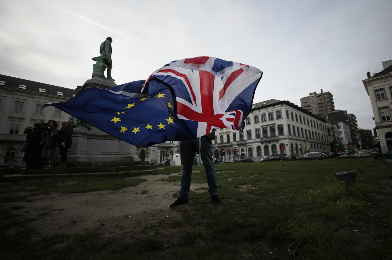 A pro-EU supporter unfurls a Union and EU flag prior to a ceremony to celebrate British and EU friendship outside the European Parliament, Brussels, Jan. 20, 2020. (AP Photo)