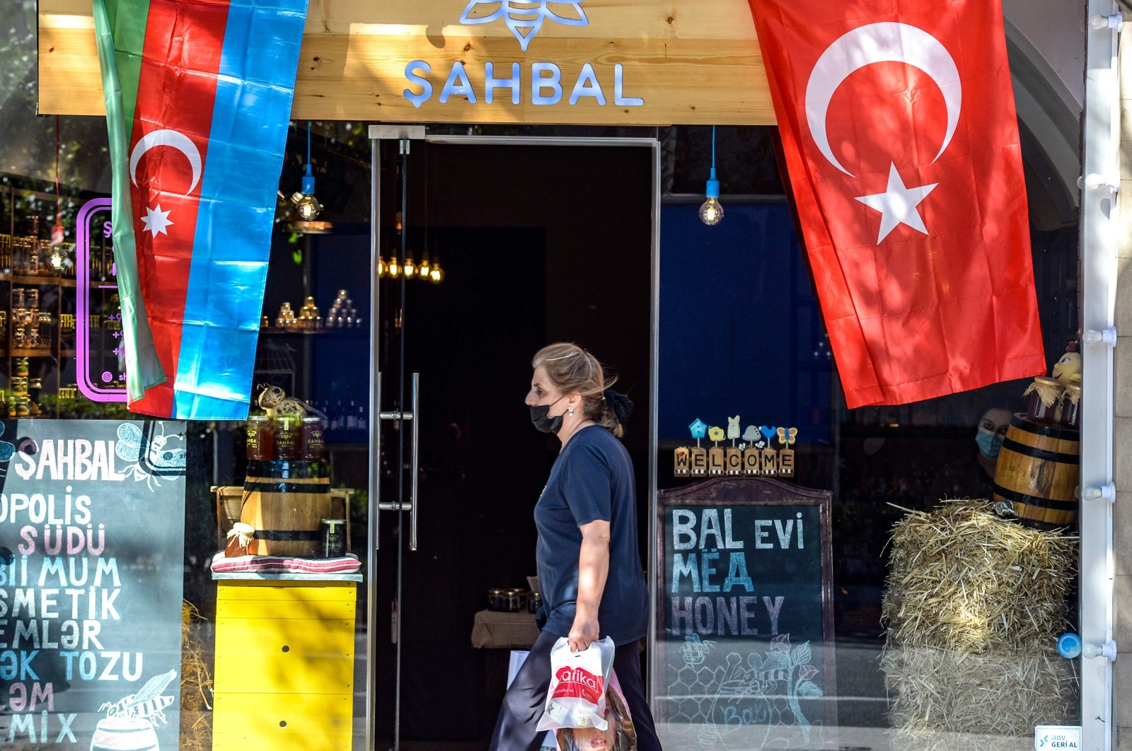 A woman walks past a shop decorated with flags of Azerbaijan and Turkey in Baku, Oct. 14, 2020. (AFP Photo)