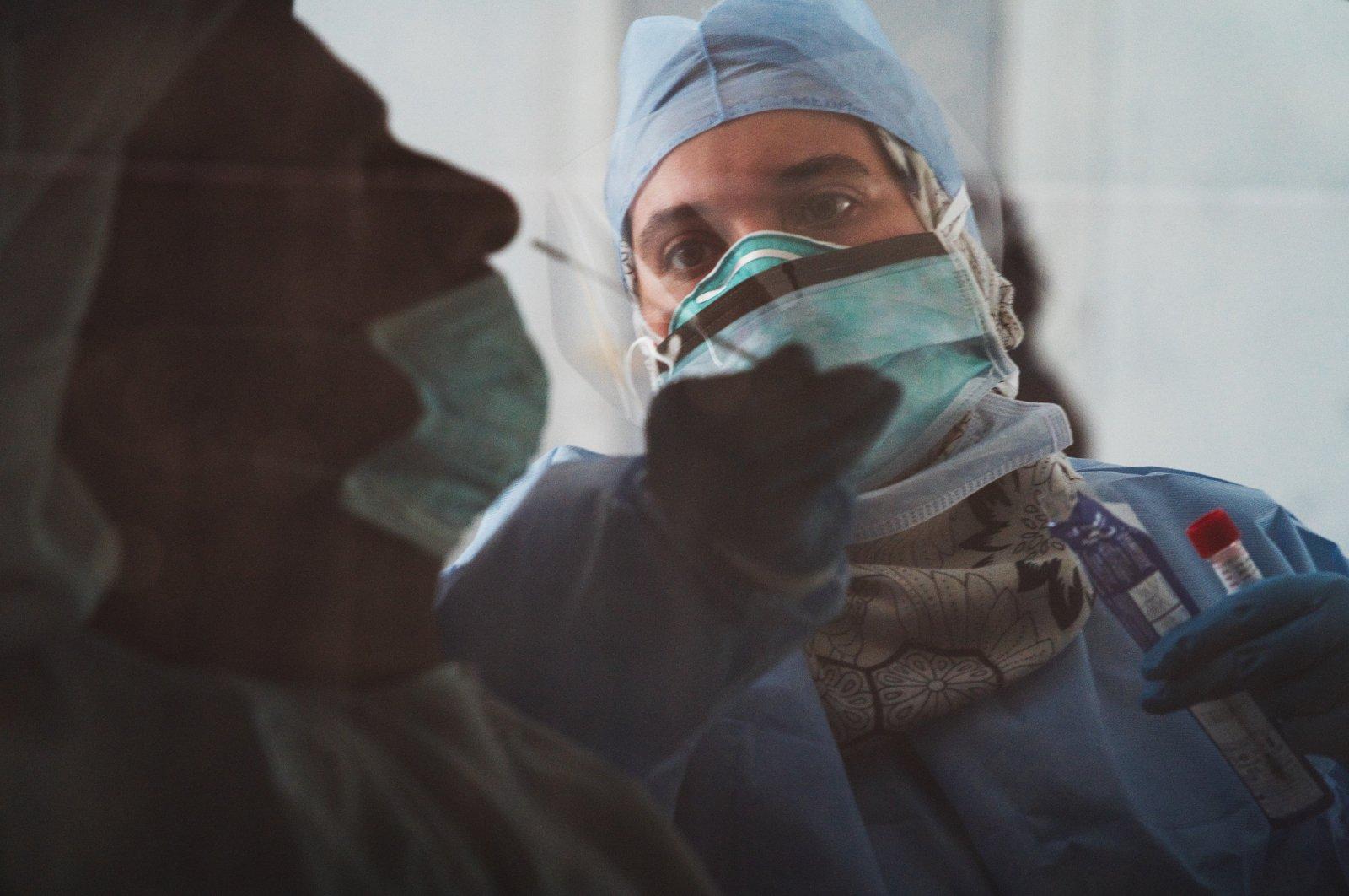 A technician takes a nasal swab for a new coronavirus detection test at a drive-thru testing facility in Abu Dhabi, United Arab Emirates, April 2, 2020. (AP Photo)