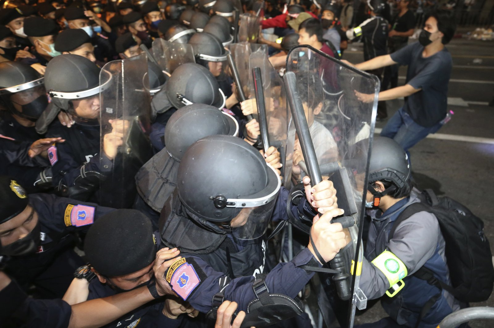 Pro-democracy protesters push Thai policemen with riot shields during a demonstration in Bangkok, Thailand, Thursday, Oct. 15, 2020. (AP Photo)