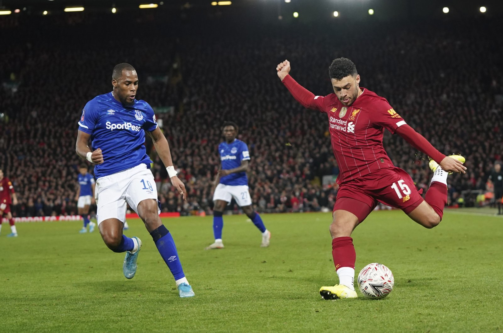 Liverpool's Alex Oxlade-Chamberlain (R) kicks the ball as Everton's Djibril Sidibe tries to stop him during an FA Cup match in Liverpool, England, Jan. 5, 2020. (AP Photo)