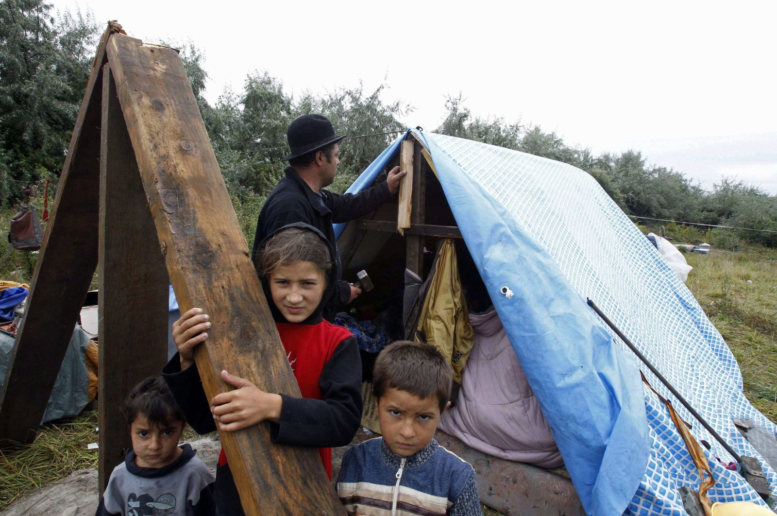 A Roma family stands outside their makeshift shelter built after police seized their caravan two weeks earlier in an illegal camp in Roubaix, near Lille, northern France, Aug. 17, 2010. (Reuters Photo)