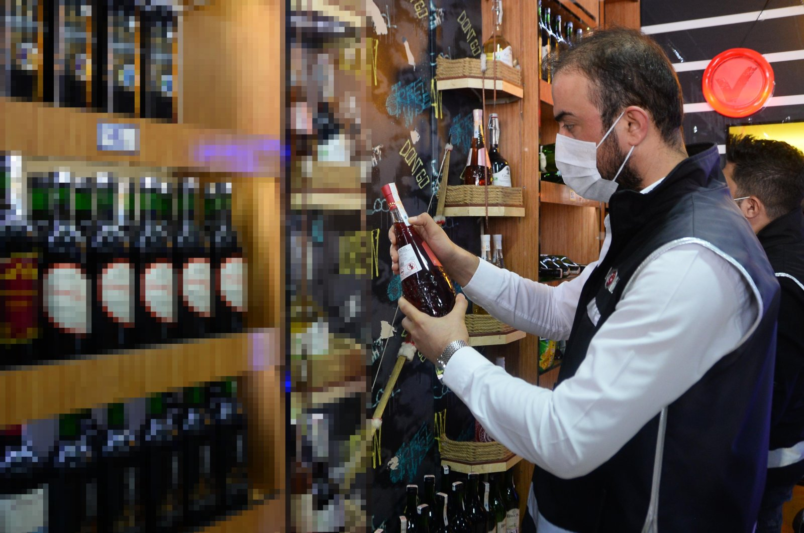 A police officer inspects a liquor store to detect possible bootleg drinks in Mersin, southern Turkey, Oct. 13, 2020. (DHA Photo)