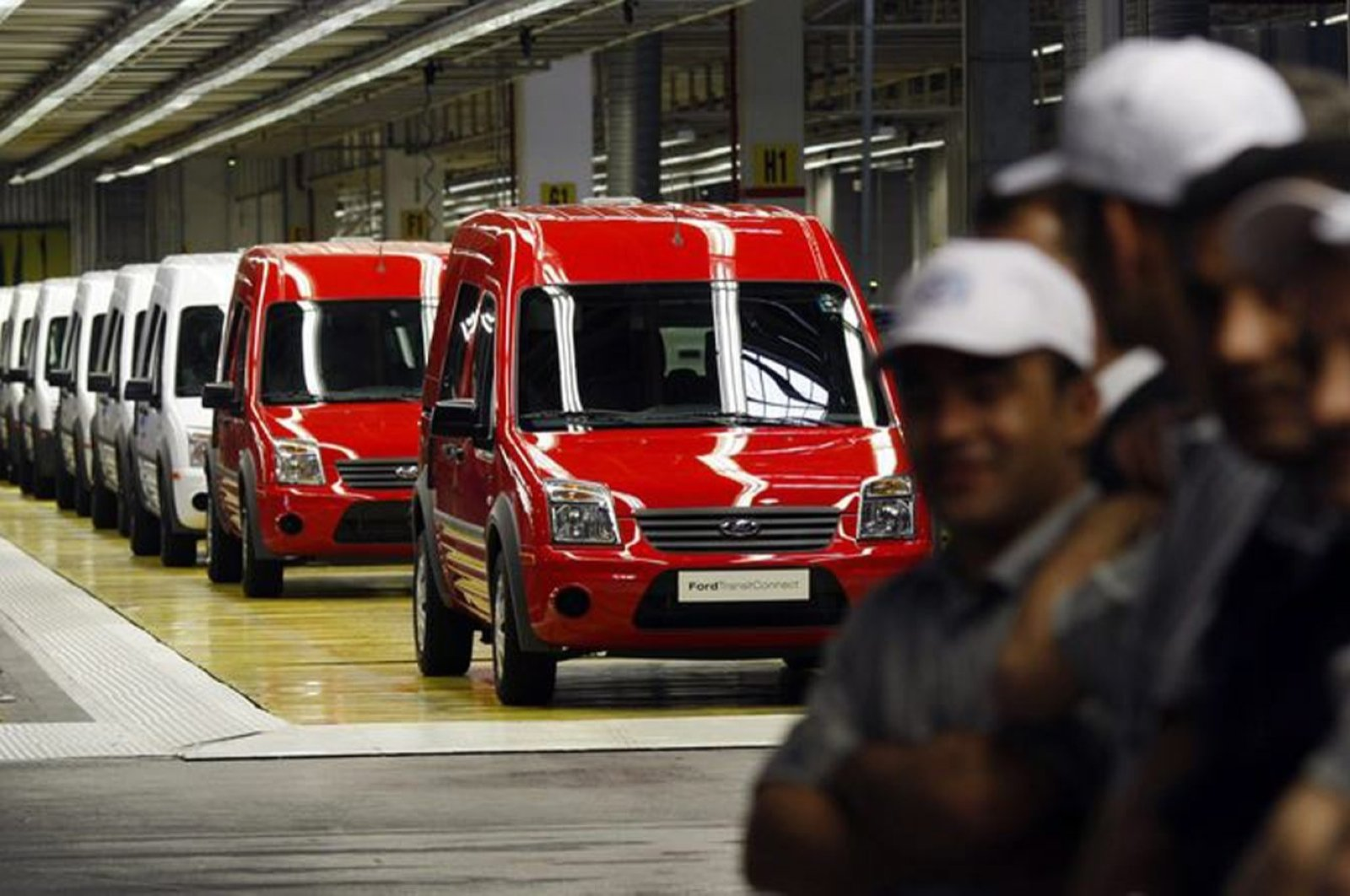 Turkish workers stand near Ford Transit Connect compact panel vans during a ceremony at the Ford Otosan Ihsaniye car plant near the western city of Kocaeli, Turkey, May 22, 2009. (Reuters Photo)