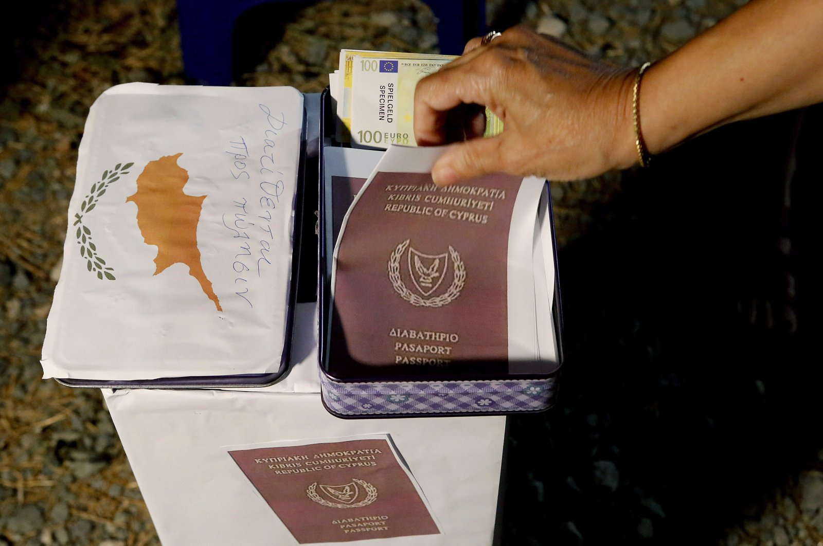 A demonstrator takes a mock copy of a Cyprus passport during a demonstration against corruption outside of the conference center, Nicosia, Oct. 14, 2020. (AP Photo)