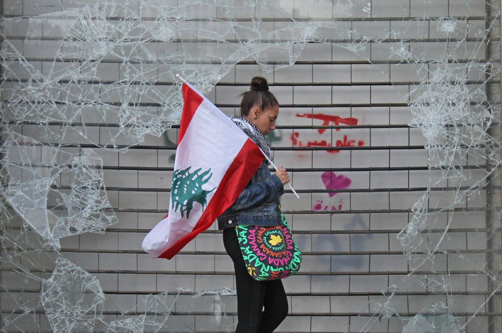 An anti-government protester walks with a Lebanese national flag past a broken window in downtown Beirut, Lebanon, Oct. 24, 2019. (AFP Photo)