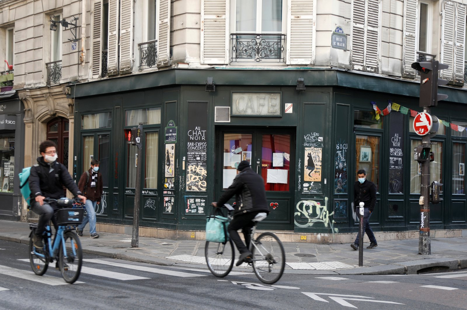 Cyclists ride past a bar closed as part of stricter restrictions, Paris, France, Oct. 13, 2020.  (Reuters Photo)