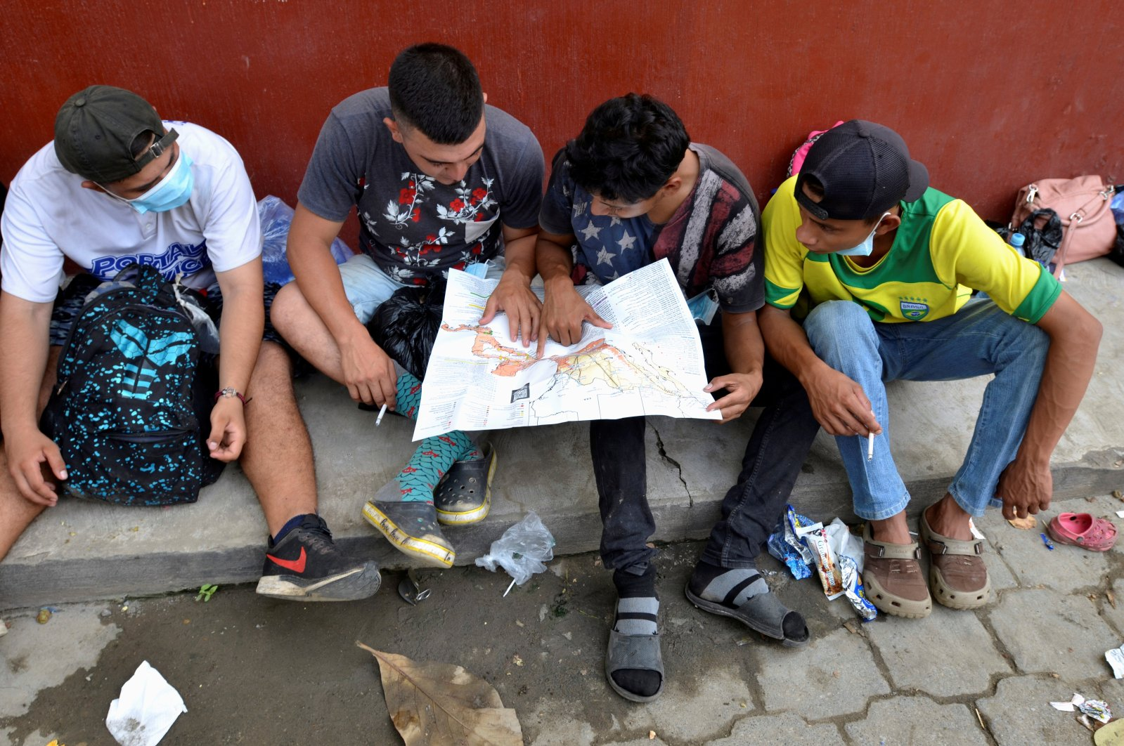 A group of Honduran migrants who are trying to reach the U.S., look at a Central America and Mexico map outside a migrant shelter as they wait to move toward the Guatemala and Mexico border, in Tecun Uman, Guatemala, Oct. 3, 2020. (Reuters Photo)