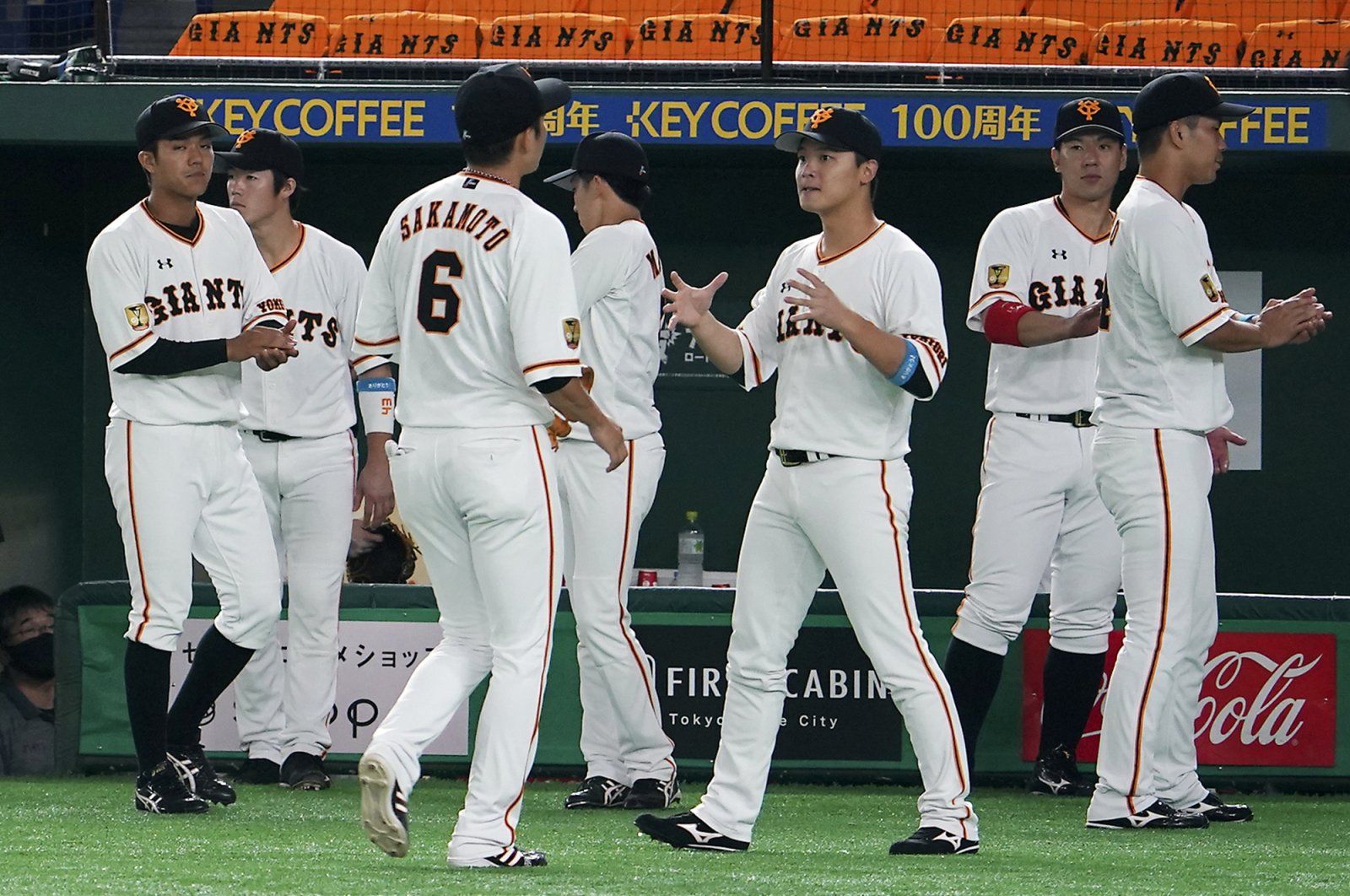 Yomiuri Giants players gather between play in an opening baseball game against the Hanshin Tigers, Tokyo, Japan, June 19, 2020. (AP Photo)