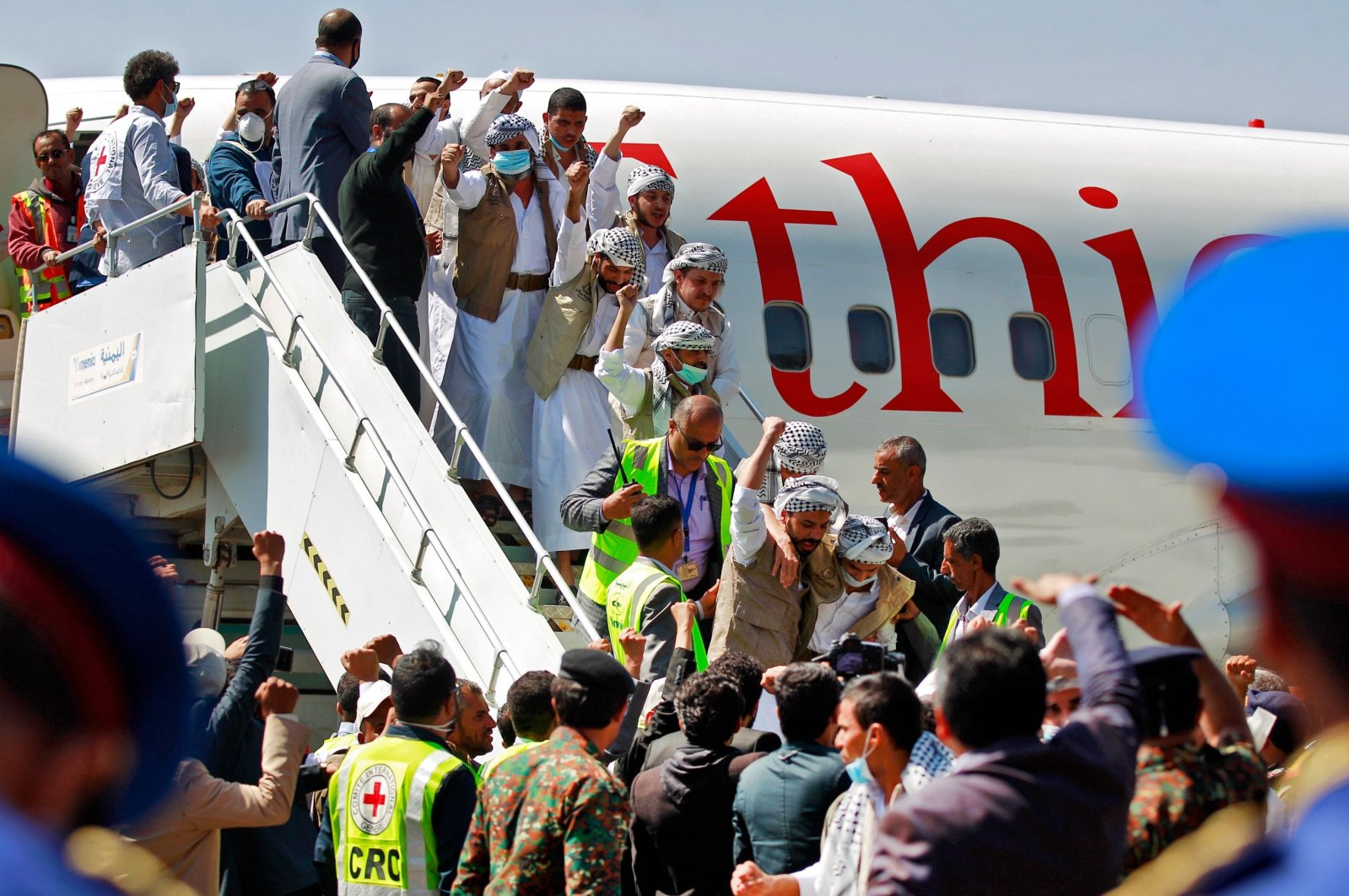 Freed Yemeni Houthi prisoners wave to the crowd as they descend the stairs of the plane that transported them after being released as the war-torn country began swapping 1,000 prisoners in a complex operation overseen by the International Committee of the Red Cross, Sanaa, Yemen, Oct. 15, 2020. (AFP Photo)