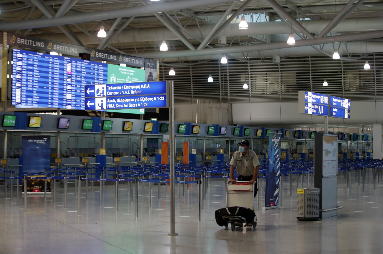 A passenger wearing a face mask walks through the empty Eleftherios Venizelos International Airport during a 24-hour strike in the public sector in Athens, Greece, Oct. 15, 2020. (AP Photo)