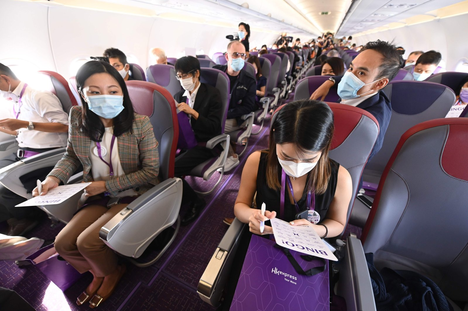 "Staff members from budget carrier HK Express take part in a preview ""Flycation"" flight around Hong Kong on Oct. 15, 2020, during an inaugural ""flight to nowhere"" journey filled with media and staff, sparking criticism from environmentalists. (AFP Photo)"