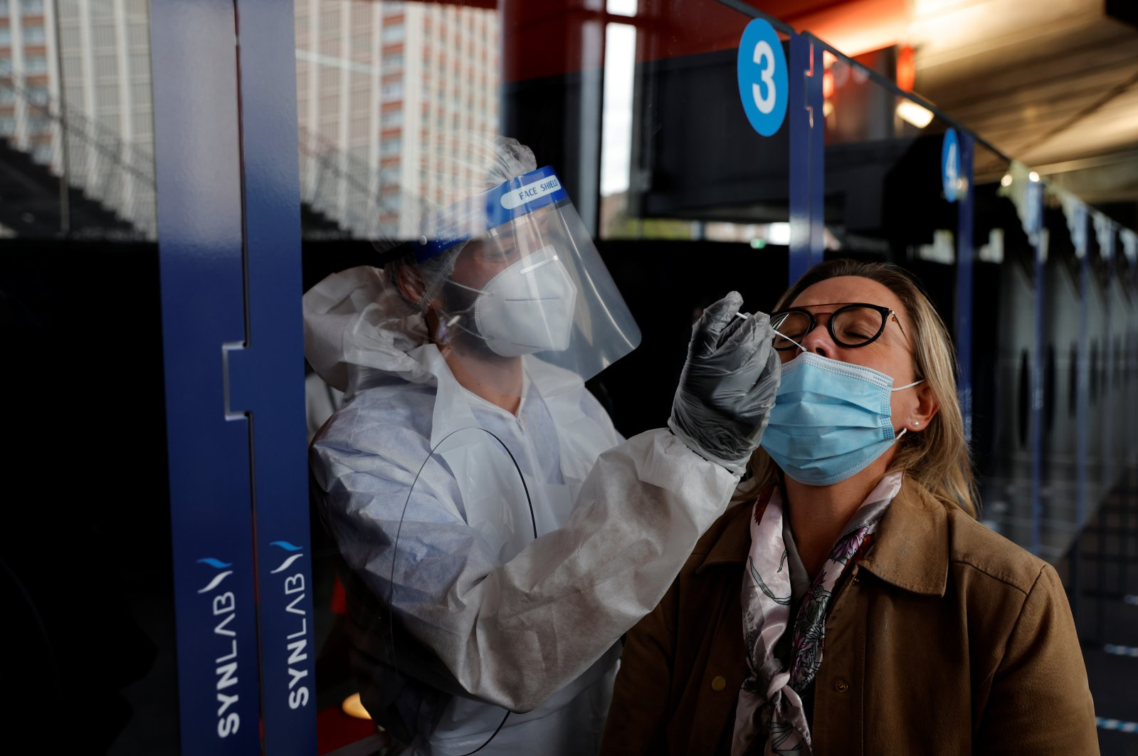A health worker, wearing a protective suit and a face mask, administers a nasal swab to a patient in a temporary testing site for the coronavirus disease (COVID-19) at the Zenith Arena in Lille, France, October 15, 2020.  (Reuters Photo)