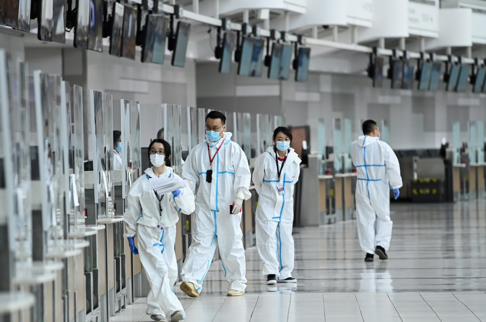 Workers walk by a check-in counter at Pearson International Airport during the COVID-19 pandemic, Toronto, Canada, Oct. 14, 2020. (AP Photo)