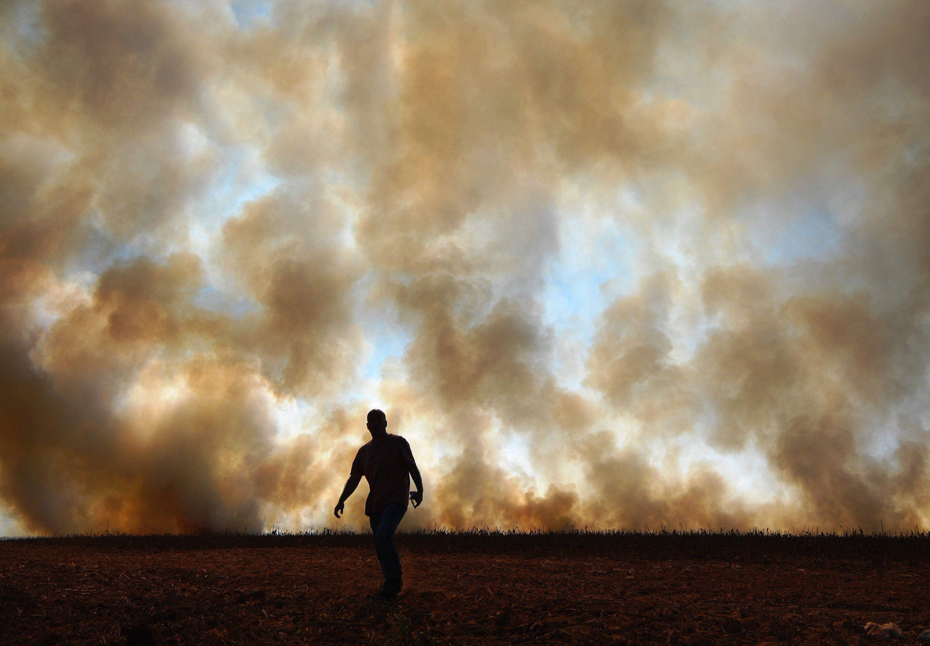 In this file photo taken on Aug. 9, 2020, a man is seen in front of smoke rising from an illegally lit fire on a maize field that borders a rainforest reserve, in Sinop, Mato Grosso state, Brazil. (AFP Photo)