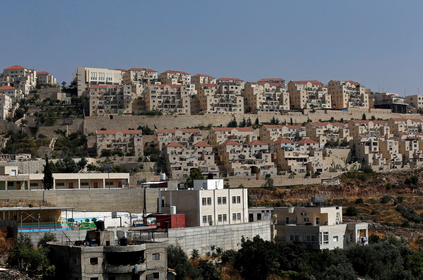 Palestinian houses in the village of Wadi Fukin, as the Jewish settlement of Beitar Illit is seen in the background in the Israeli-occupied West Bank, June 23, 2019.  (REUTERS Photo)