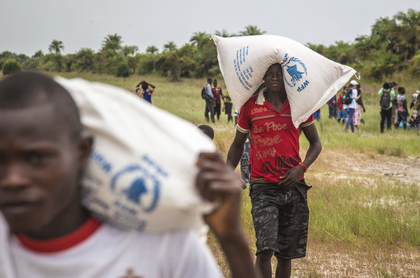 People carry food aid from the United Nations World Food Program agency, Dec. 7, 2014. (AP Photo)