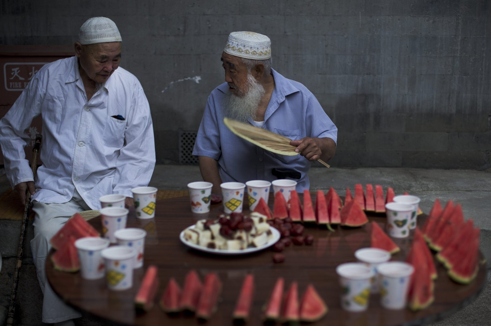 Chinese Muslim men chat as they wait for the time to break their fast during the Muslim holy month of Ramadan at Niujie Mosque, the oldest and largest mosque in Beijing, China, July 2, 2014. (AP Photo)