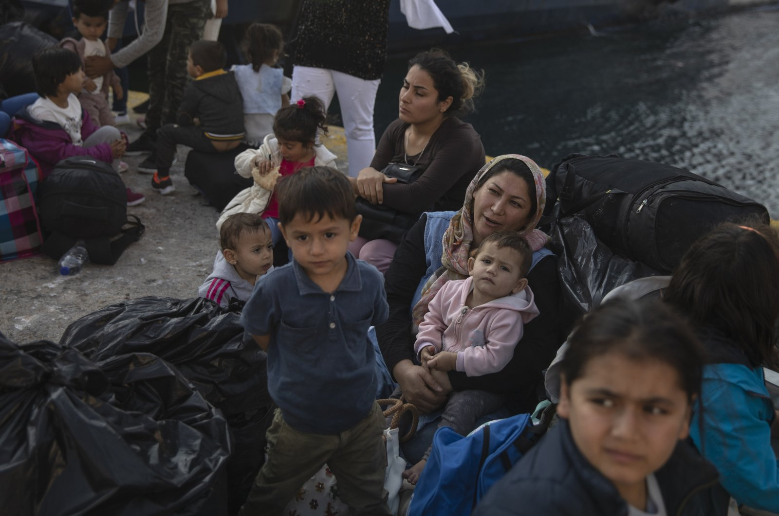 Refugees and migrants wait for buses after their arrival to the port of Elefsina, near Athens, Greece, Oct. 22, 2019. (AP Photo)