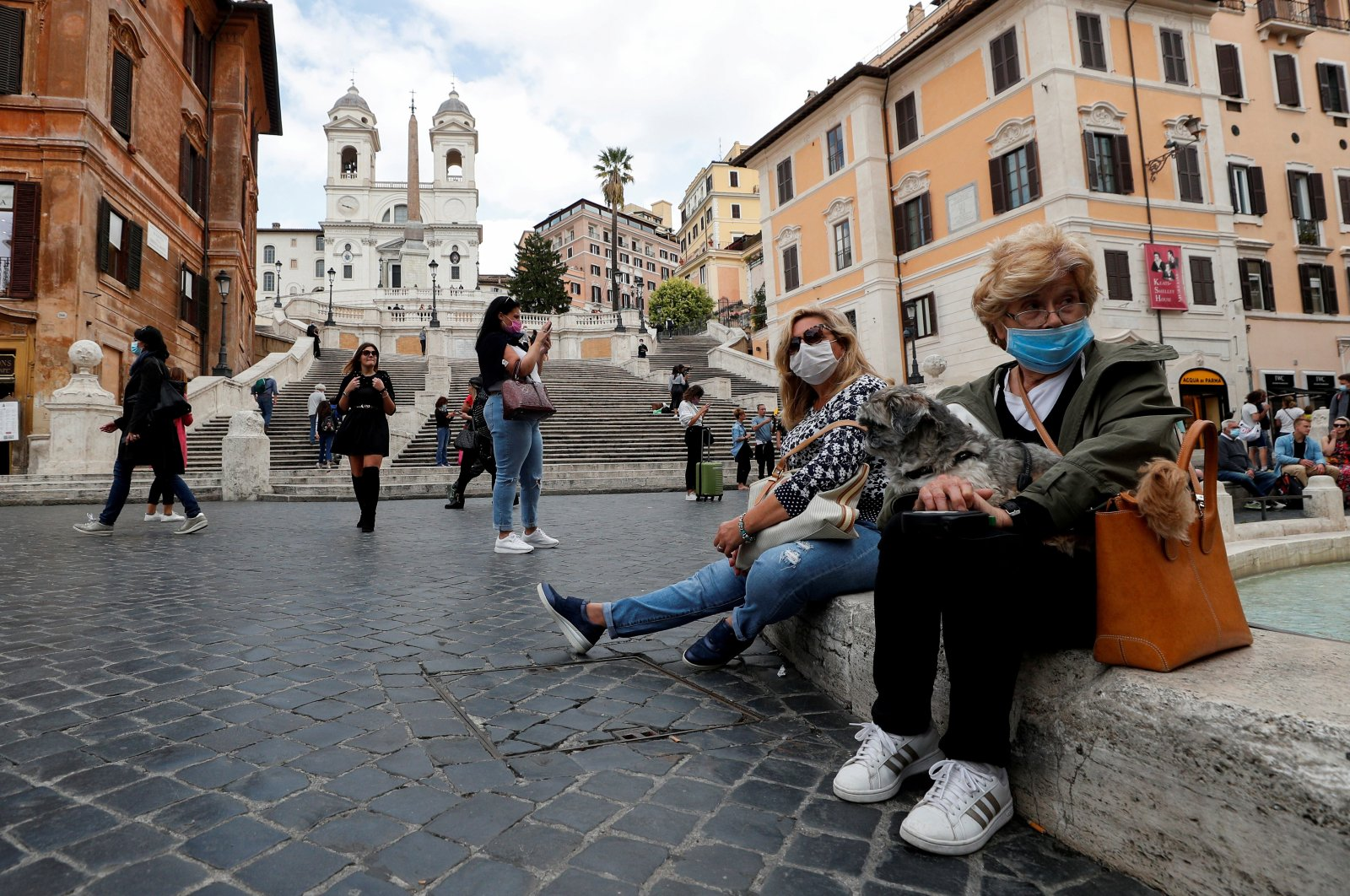 Women wearing face masks sit next to the Spanish Steps, as local authorities in the Italian capital Rome order face coverings to be worn at all times out of doors in an effort to counter rising coronavirus disease (COVID-19) infections, in Rome, Italy, Oct. 2, 2020. (Reuters Photo)
