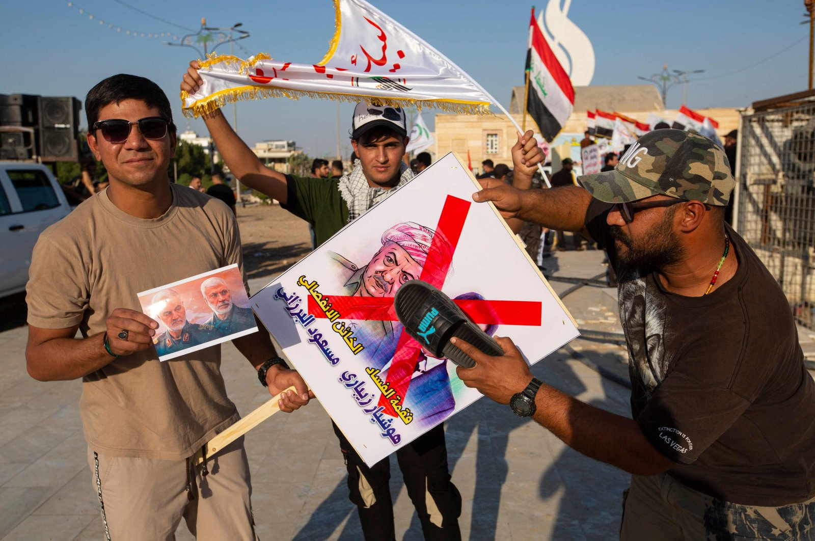 A supporter of Hashed al-Shaabi hits a poster bearing the portraits of Kurdish ex-minister Hoshyar Zebari and Kurdish leader Masoud Barzani with a slipper while a fellow protester carries the portraits of slain Iranian commander Qassem Soleimani and Iraqi paramilitary commander Abu Mahdi Al-Muhandis during a protest in support of the Hashed in the southern Iraqi city of Basra on October 17, 2020. (AFP Photo)