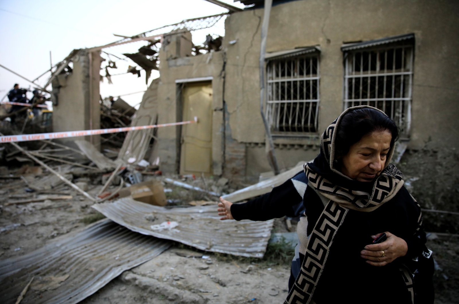 Hicran Quliyeva reacts as she stands in front of her house at a blast site hit by a rocket during the fighting over the illegally occupied region of Nagorno-Karabakh, in the city of Ganja, Azerbaijan, Oct. 17, 2020. (Reuters Photo)