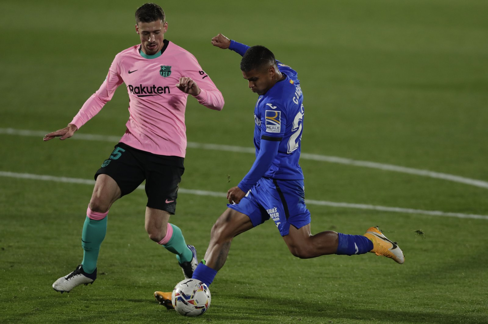Getafe's Cucho Hernandez (R) takes a shot with Barcelona's Sergio Busquets trying to interrupt during a La Liga match in Getafe, Spain, Oct. 17, 2020. (AP Photo)