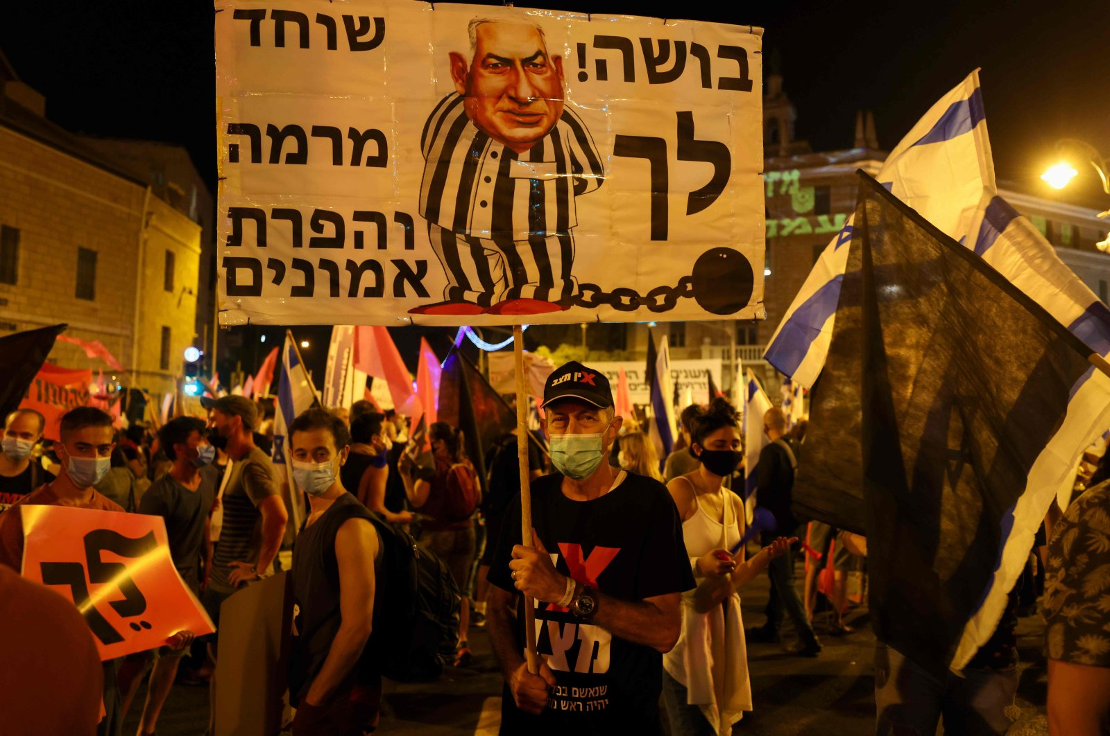 A protester carries a placard with a cartoon depicting Israeli Prime Minister Benjamin Netanyahu dressed in prison stripes and shackled with a ball and chain during a demonstration near the prime minister's residence in Jerusalem, Oct. 17, 2020. (AFP Photo)