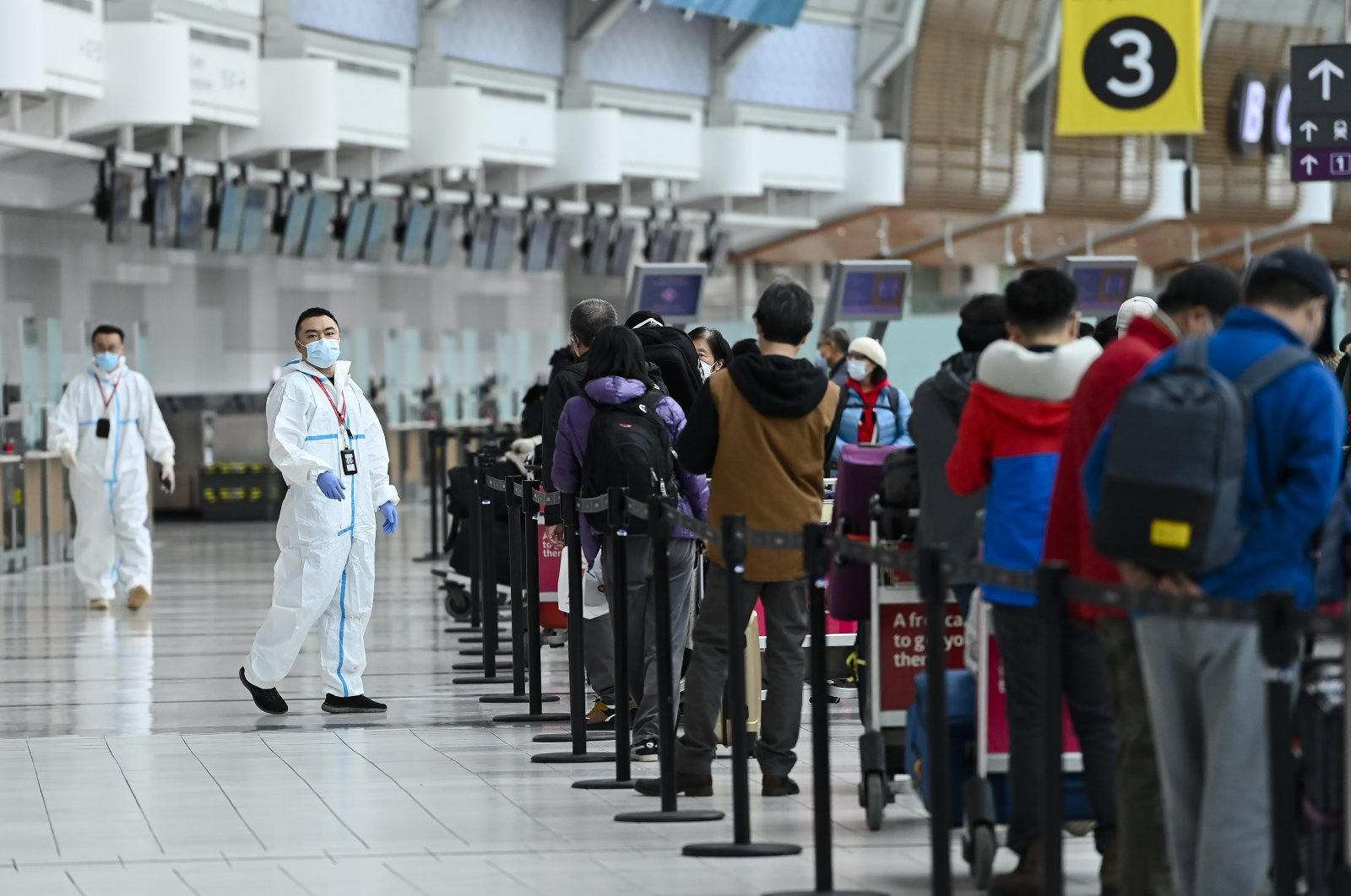 People line up and check-in for an international flight at Pearson International airport during the COVID-19 pandemic in Toronto, Canada, Oct. 14, 2020. (AP Photo)