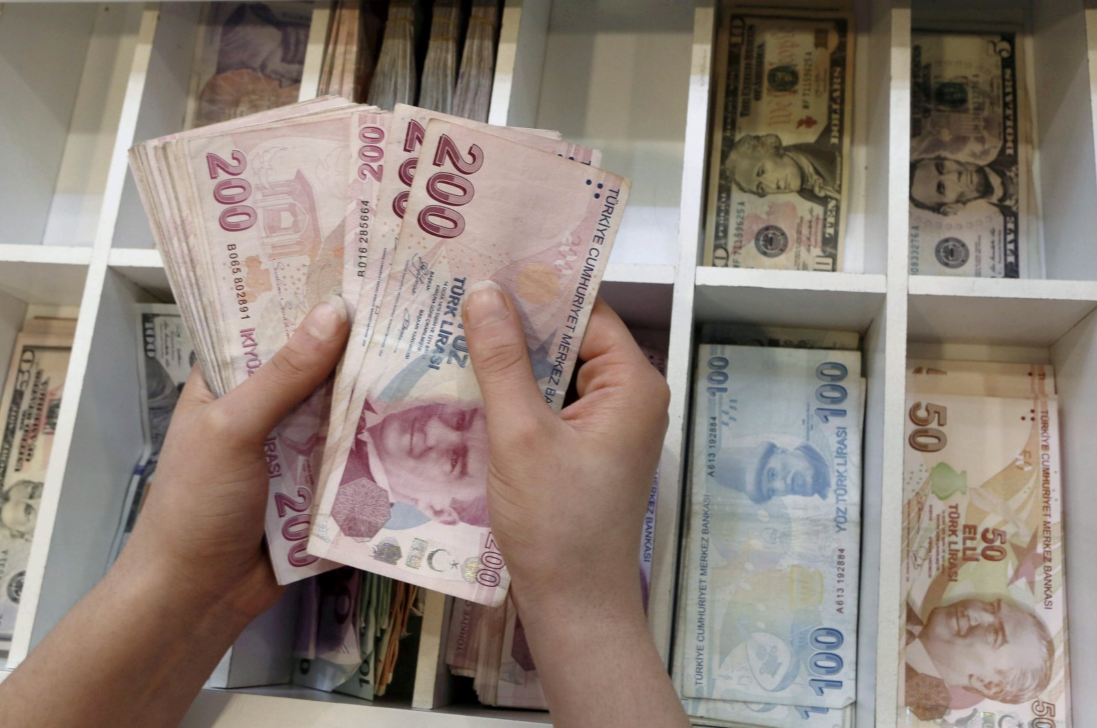 A money changer counts Turkish lira bills at an currency exchange office in central Istanbul, Turkey, August 21, 2015. (Reuters Photo)