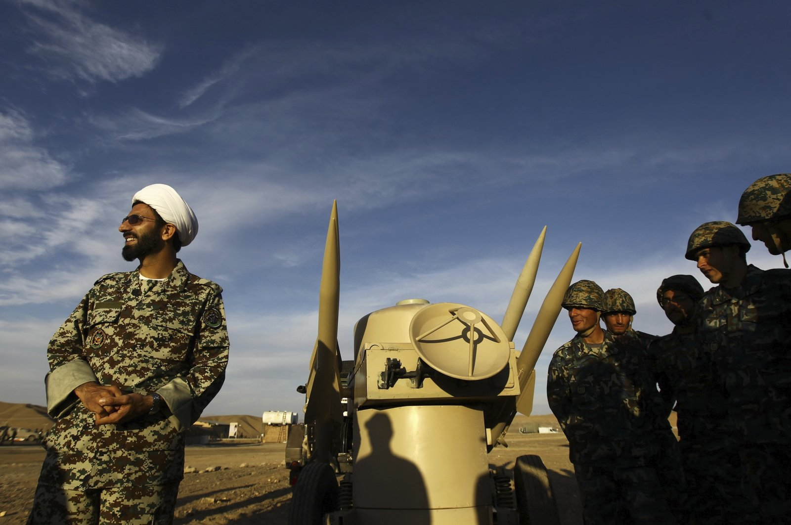 An Iranian clergyman stands next to missiles and army troops during a maneuver in an undisclosed location in Iran, Nov. 13, 2012. (AP Photo)
