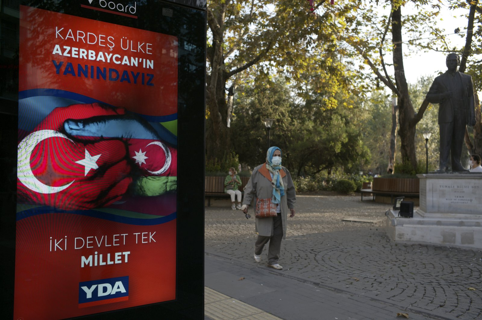 """A woman wearing a mask to help protect against the spread of coronavirus, walks past a billboard reading, """"Turkey and Azerbaijan, two states one nation,"""" in Ankara, Turkey, Monday, Oct. 12, 2020. (AP Photo)"""