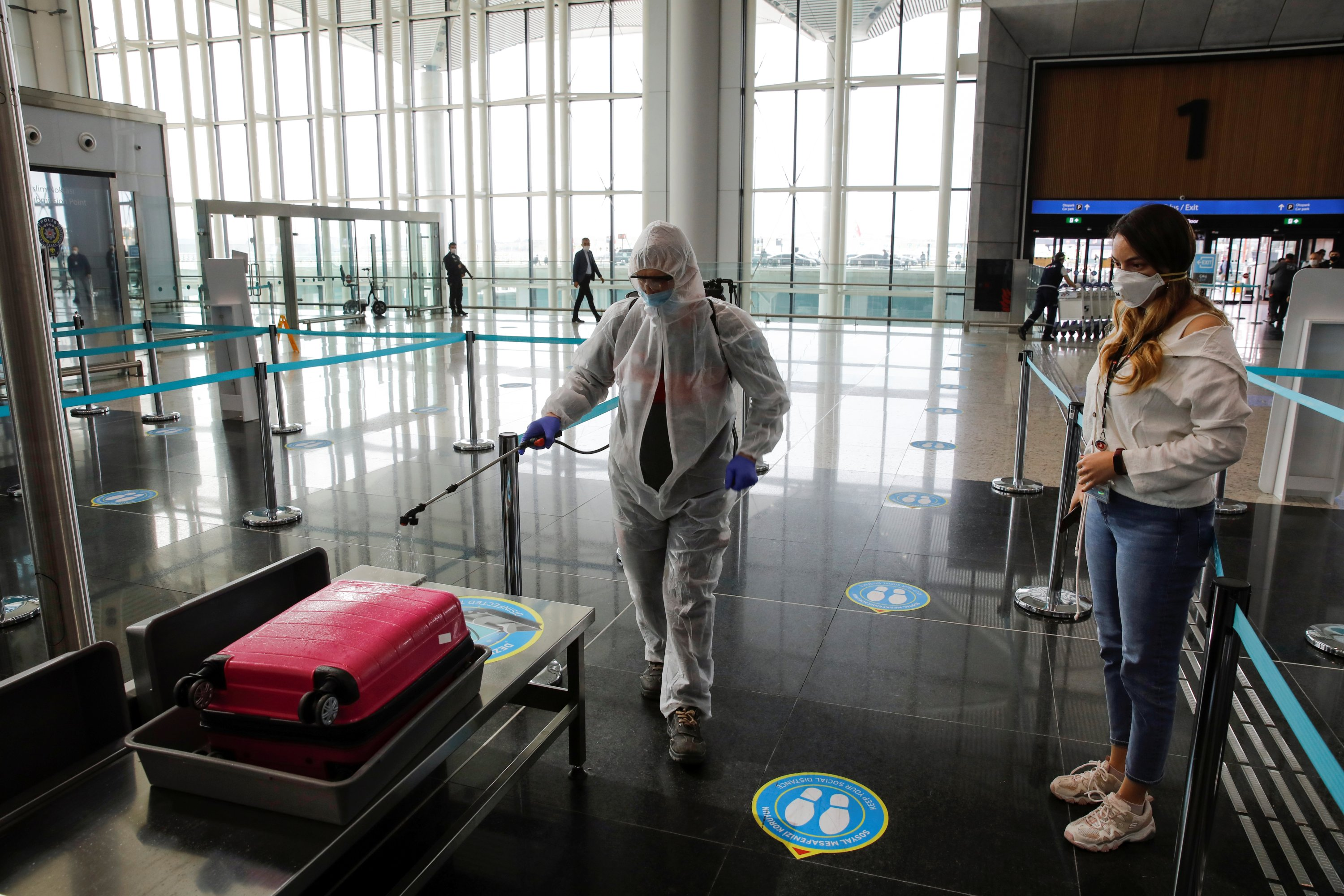 An employee wearing a protective suit disinfects luggage at the Istanbul Airport, June 1, 2020. (REUTERS Photo)