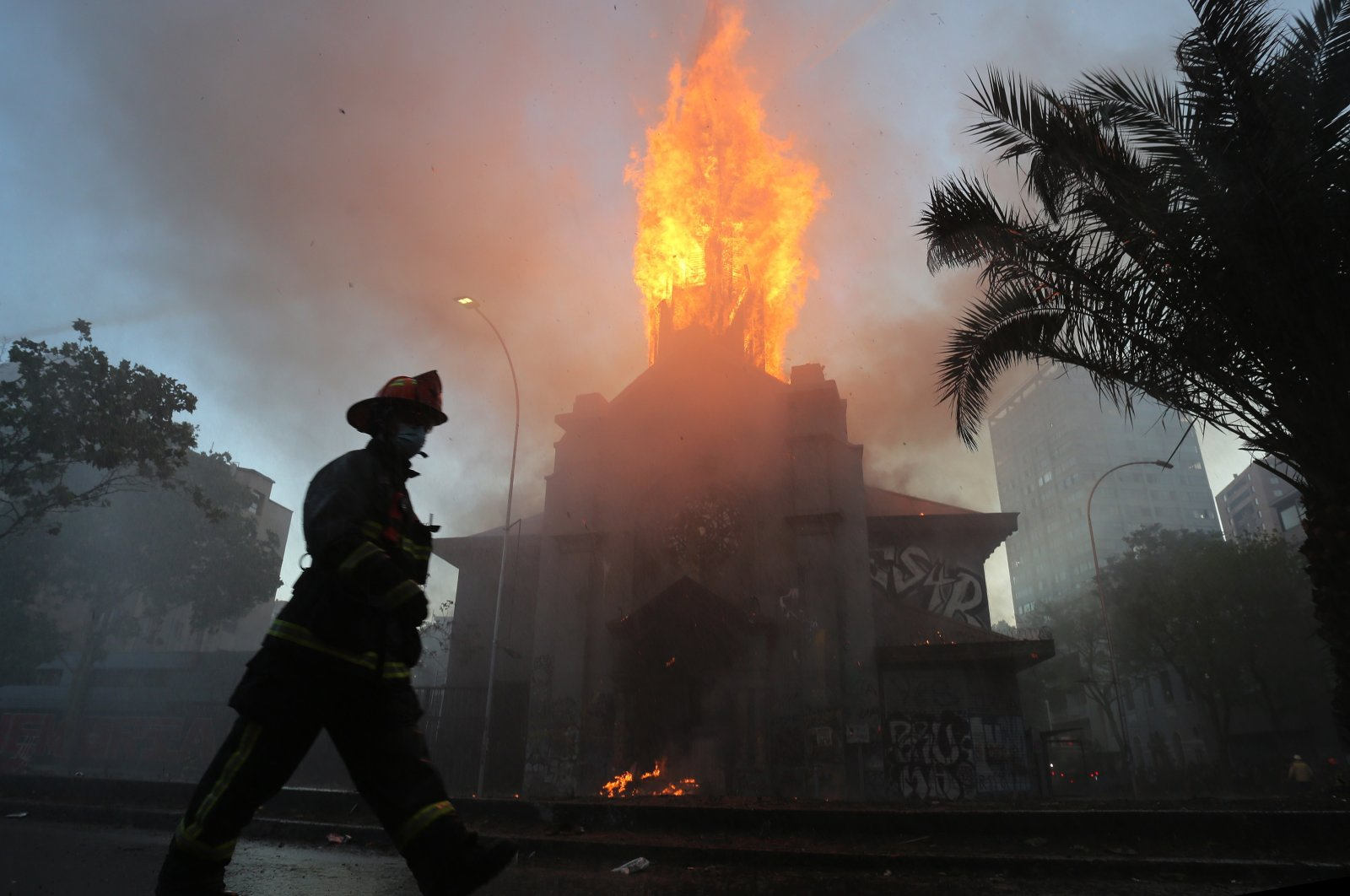 Firefighters work to extinguish a fire near Plaza Italia in the parish of La Asuncion, in the aftermath of a protest in Santiago, Chile, Oct. 18, 2020. (EPA Photo)