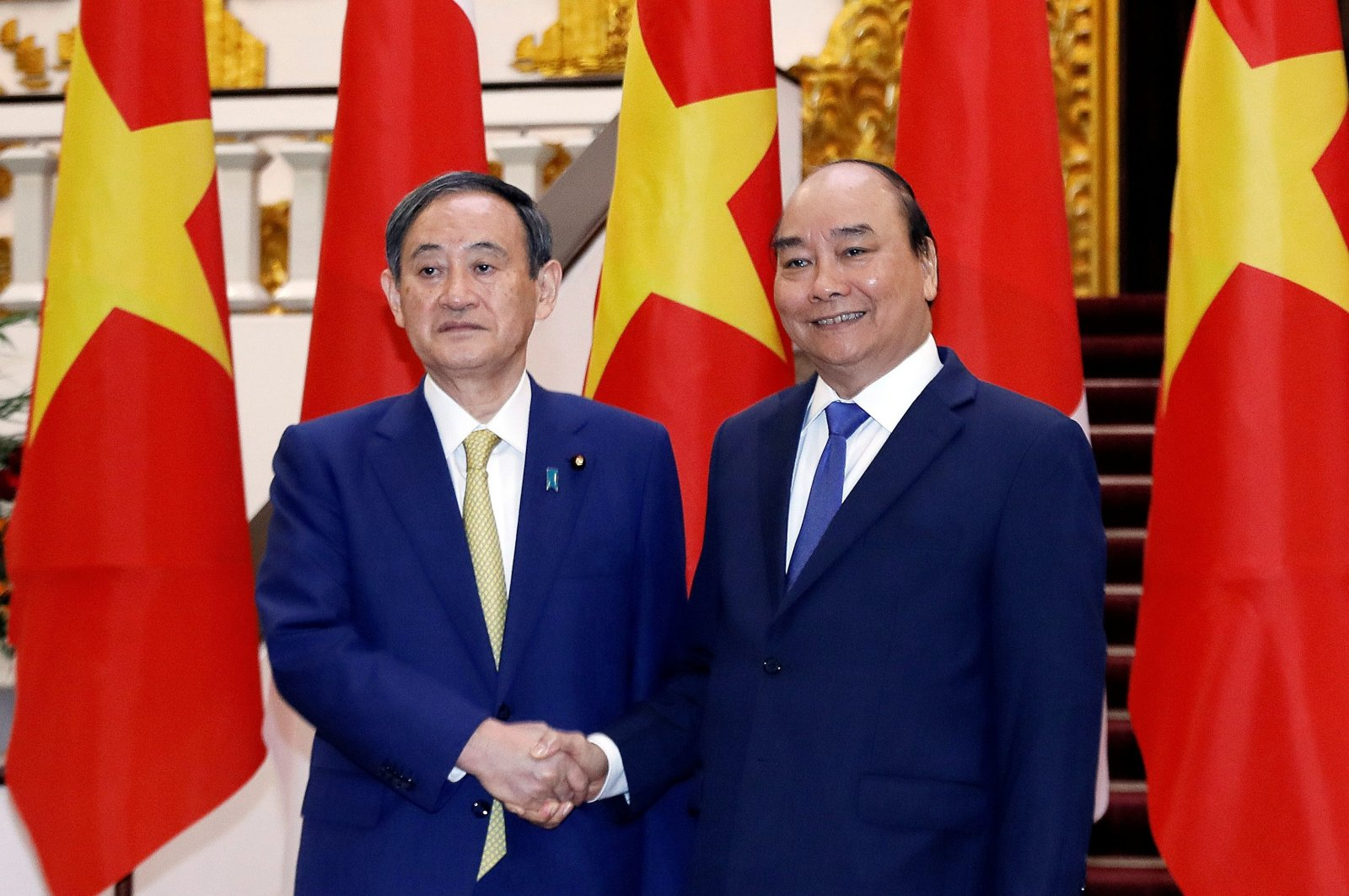 Japan's Prime Minister Yoshihide Suga (L) shakes hands with his Vietnamese counterpart Nguyen Xuan Phuc (R) during an official visit to the Government Office in Hanoi on Oct. 19, 2020. (AFP Photo)