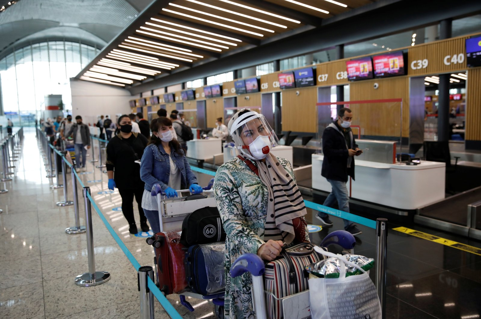 Passengers wearing face masks stand in a queue at the Istanbul Airport, June 1, 2020. (REUTERS Photo)
