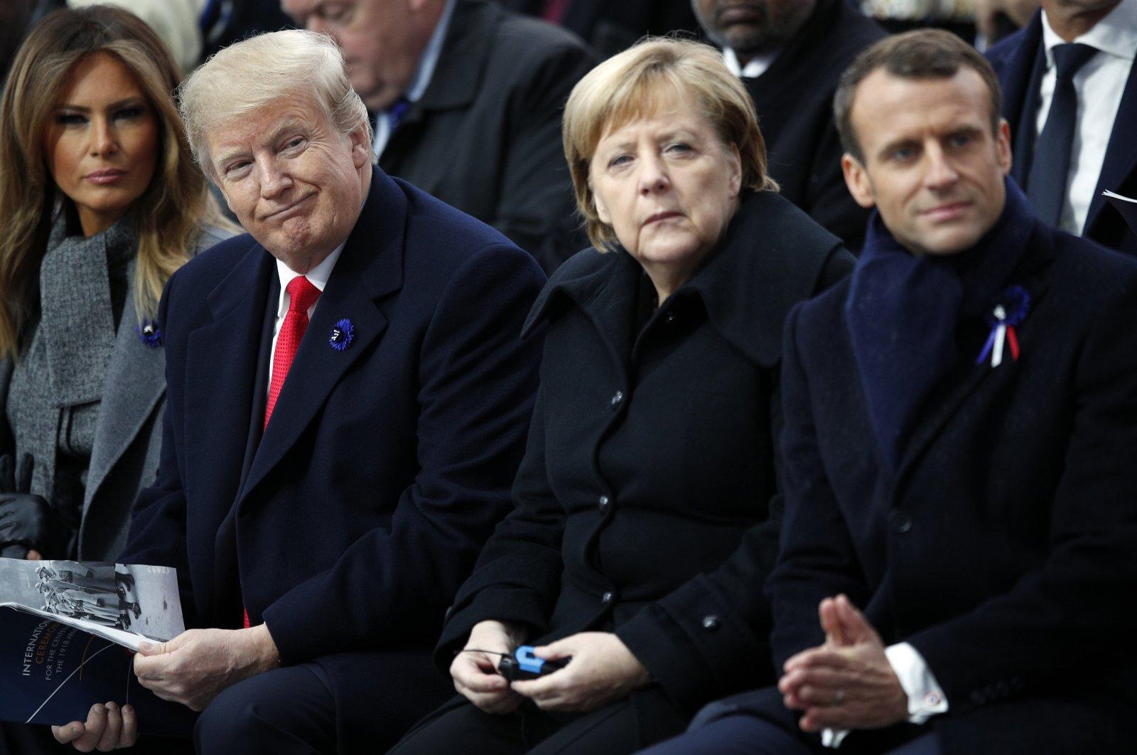 U.S President Donald Trump, German Chancellor Angela Merkel and French President Emmanuel Macron attend ceremonies at the Arc de Triomphe, Paris, Nov. 11, 2018. (AP Photo)