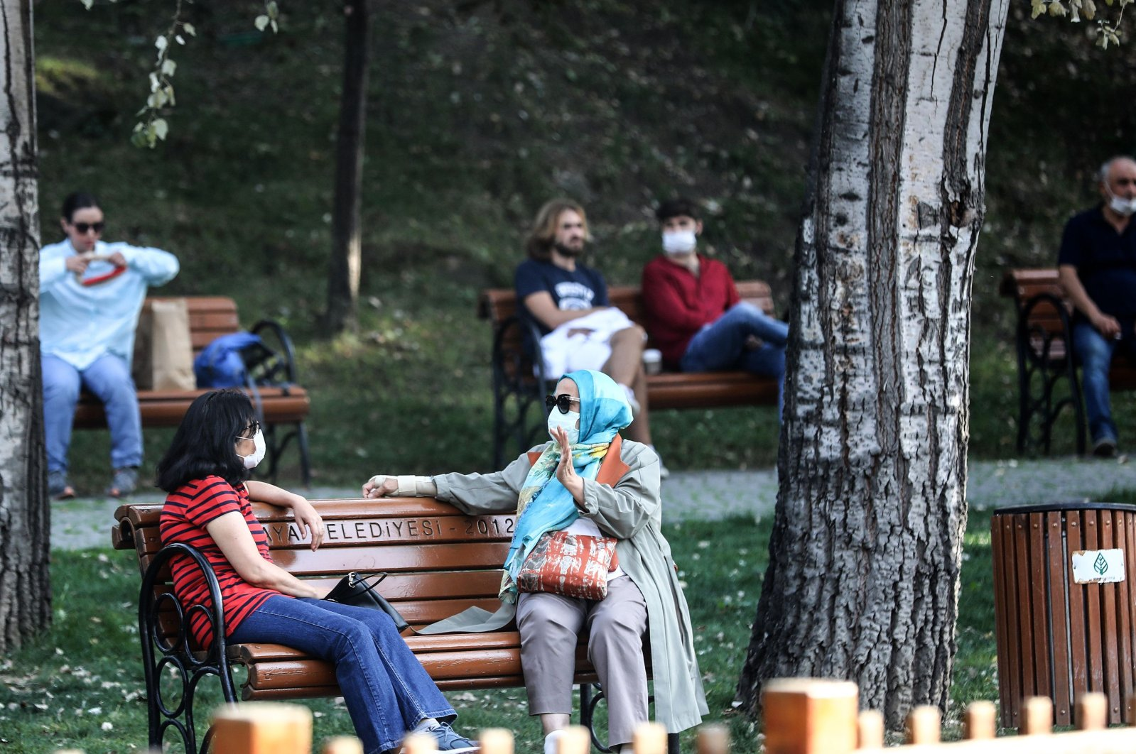 People wearing protective masks sit on benches in the Kuğulu Park in the capital Ankara, Turkey, Oct. 12, 2020. (AFP Photo)
