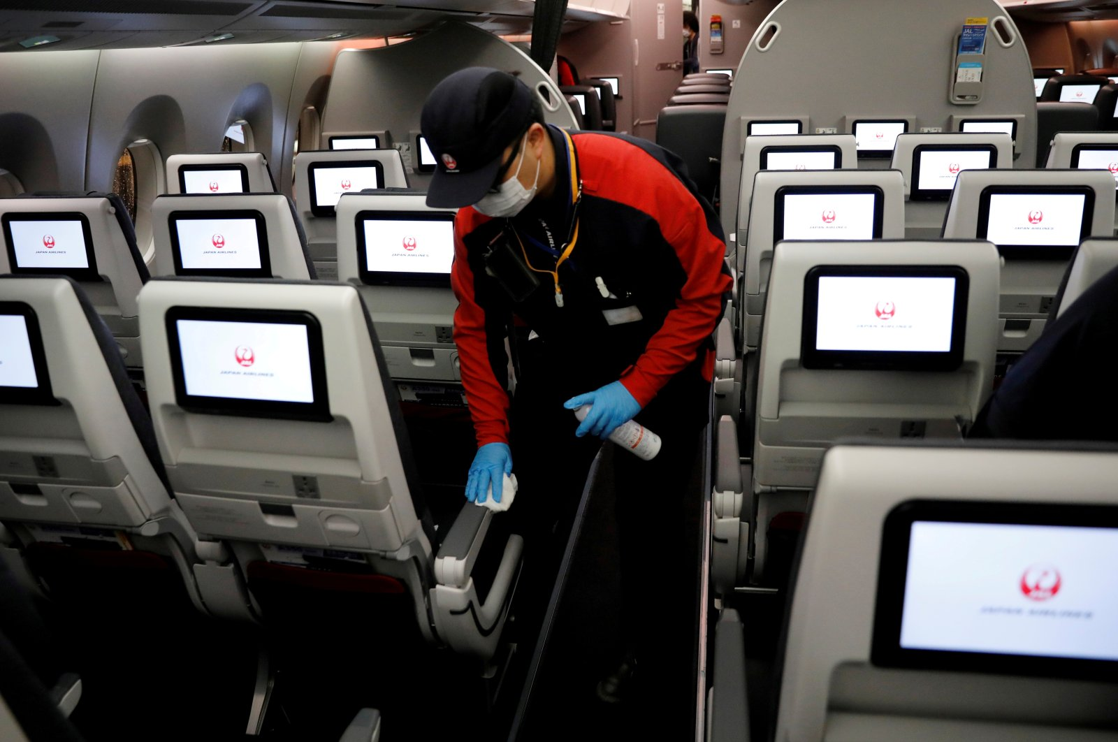 A staff member of Japan Airlines wearing a protective face mask and gloves cleans the cabin of a plane after performing a domestic flight as passengers disembarked at Haneda airport on the first day after the Japanese government lifted the state of emergency, Tokyo, Japan, May 26, 2020. (Reuters Photo)