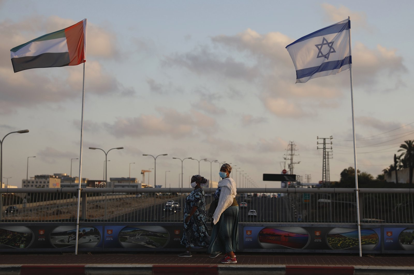 Women wearing masks against the coronavirus walk past the United Arab Emirates (UAE) and Israeli flags in Netanya, Israel, Aug. 16, 2020. (AP Photo)