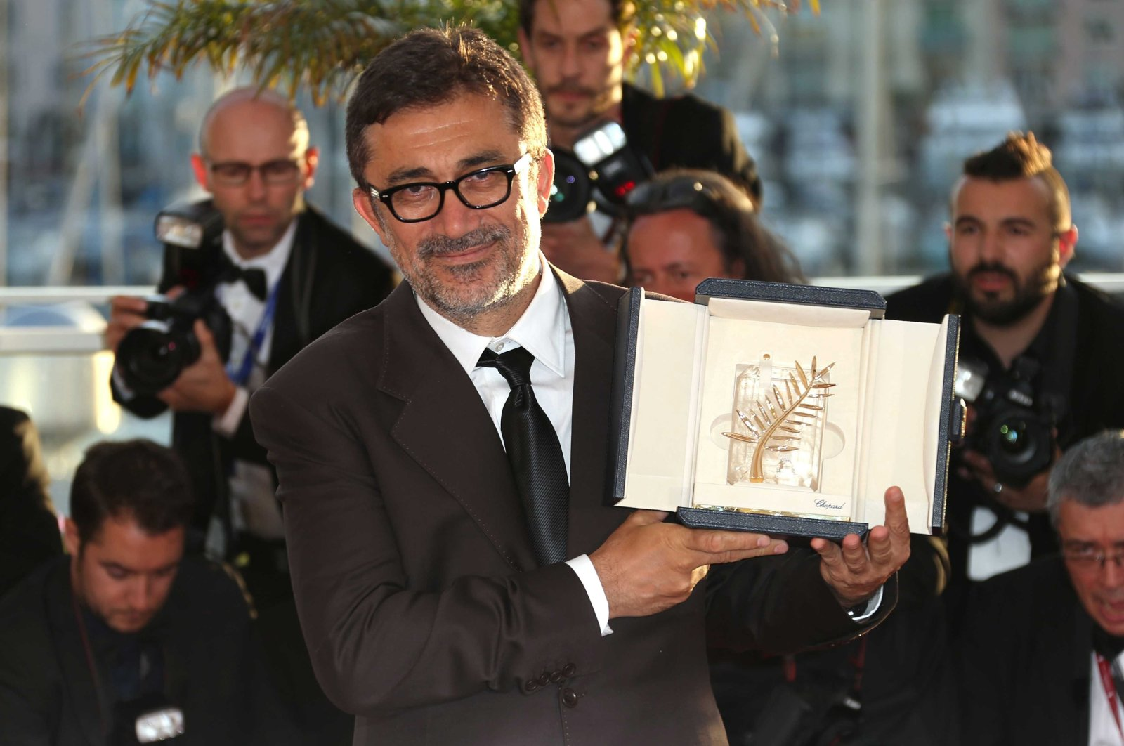 """Director Nuri Bilge Ceylan poses with the Palme d'Or award for the film """"Winter Sleep"""" during a photo-call following the awards ceremony at the 67th international film festival, Cannes, southern France, May 24, 2014. (AP PHOTO)"""