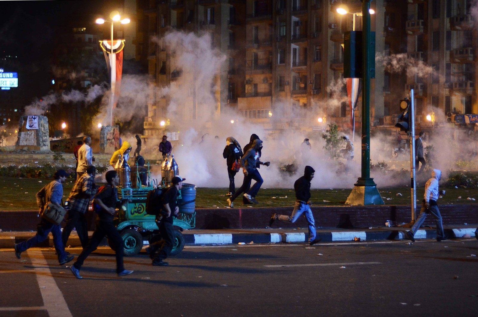 Egyptian anti-military demonstrators run for cover from tear gas fired by riot police during clashes in Tahrir Square in Cairo on Nov. 19, 2013. (AFP Photo)