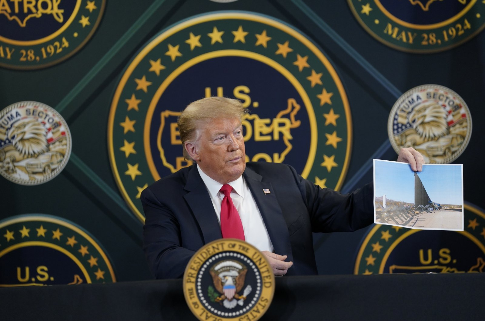 President Donald Trump holds an image of the U.S. border wall being built between the U.S. and Mexico as he participates in a border security briefing at the United States Border Patrol Yuma Station in Yuma, Arizona, June 23, 2020. (AP Photo)