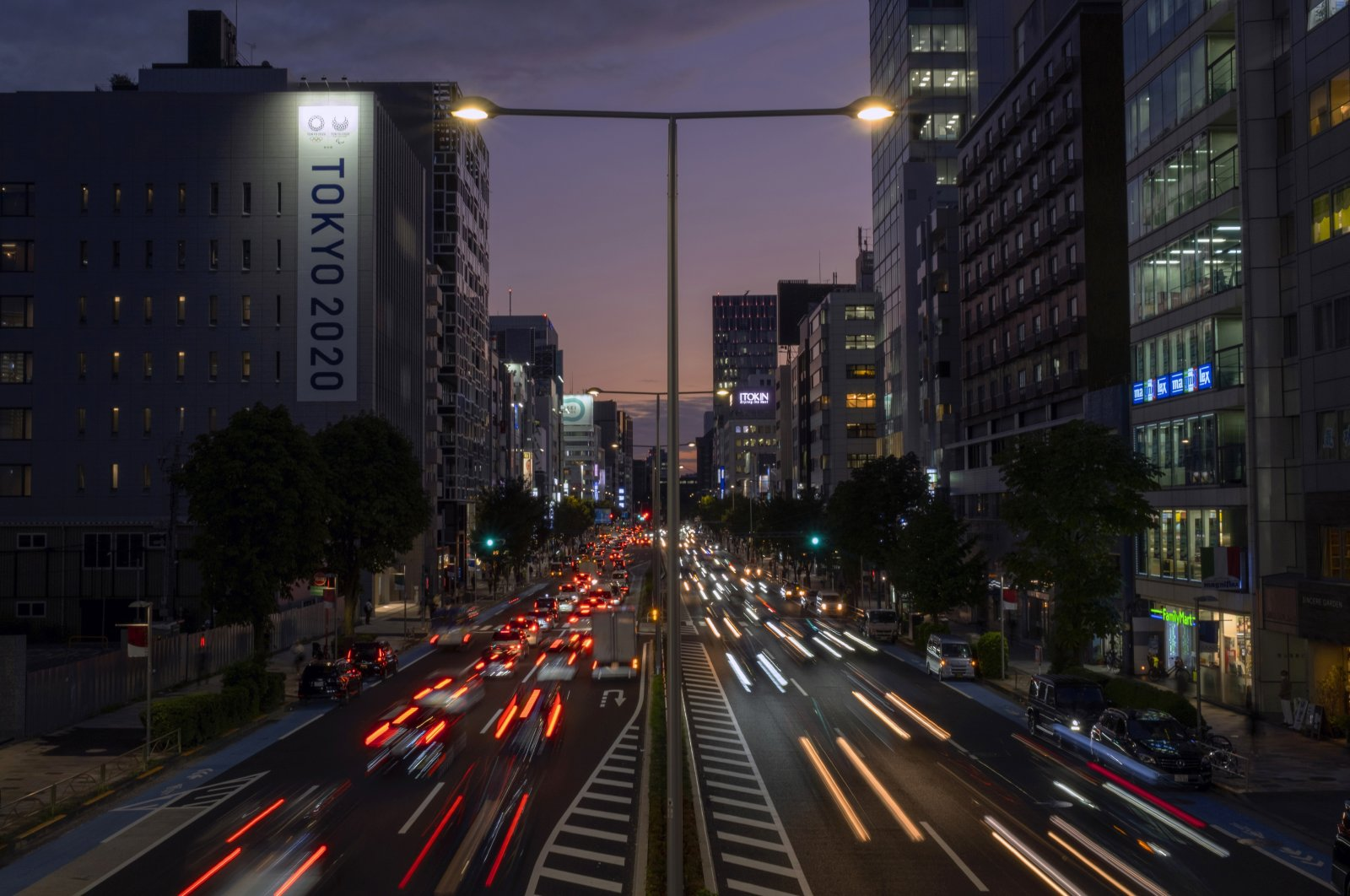 This long exposure photo shows streaks of lights from the cars passing by a Tokyo 2020 Olympics and Paralympics sign on the side of a building in Tokyo, as the sky is colored by the sunset, Oct. 12, 2020. (AP Photo / Kiichiro Sato)