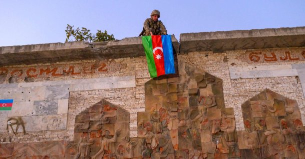 A soldier hangs Azerbaijan's flag in the city of Jabrayil, where Azerbaijani forces regained control during combat with Armenia over the breakaway region of Nagorno-Karabakh, Oct. 16, 2020. (AFP Photo)