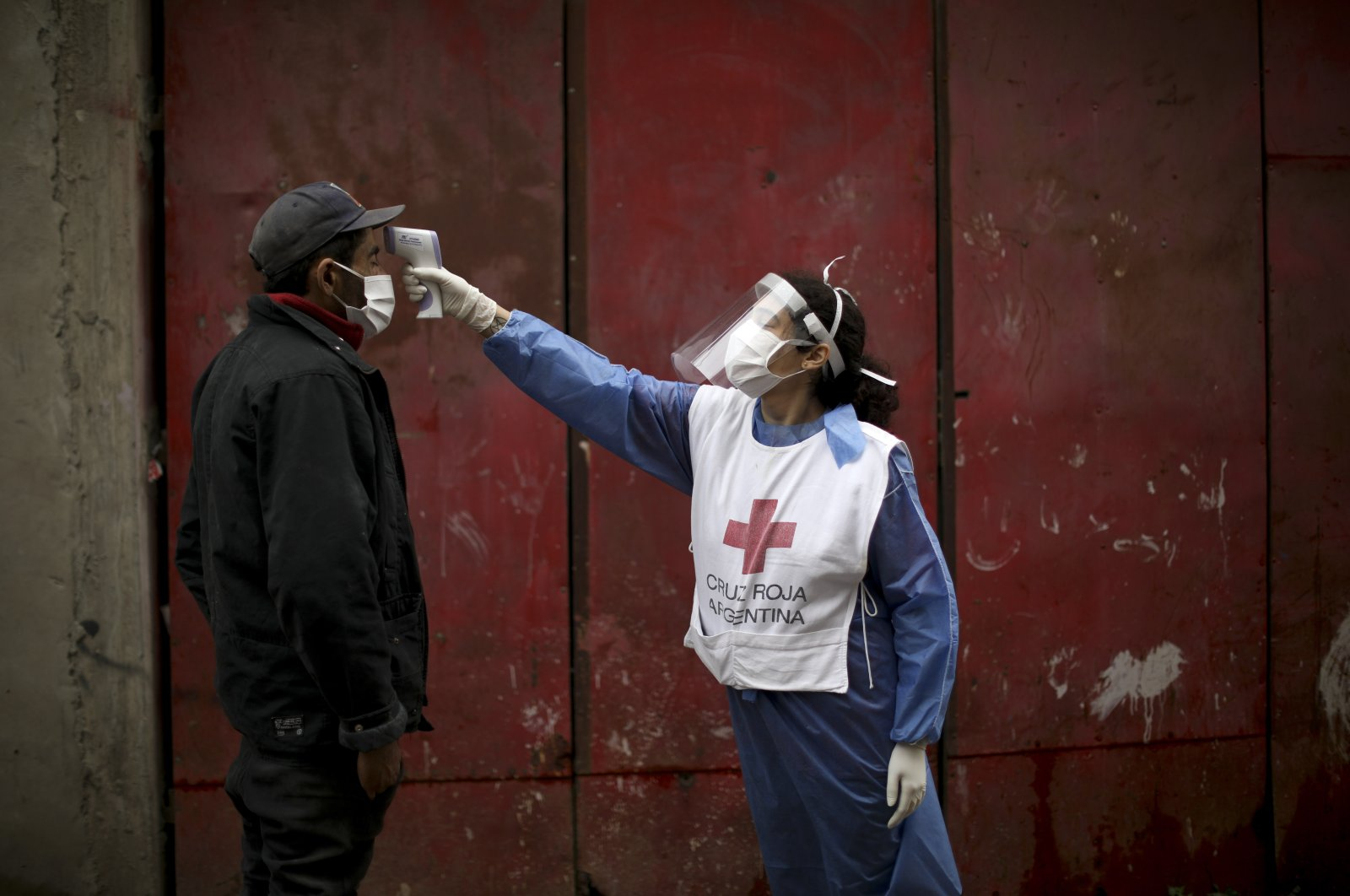 A Red Cross volunteer measures the temperature of a man inside the Fraga slum during a government-ordered lockdown to curb the spread of the new coronavirus, in Buenos Aires, Argentina, June 6, 2020. (AP Photo)
