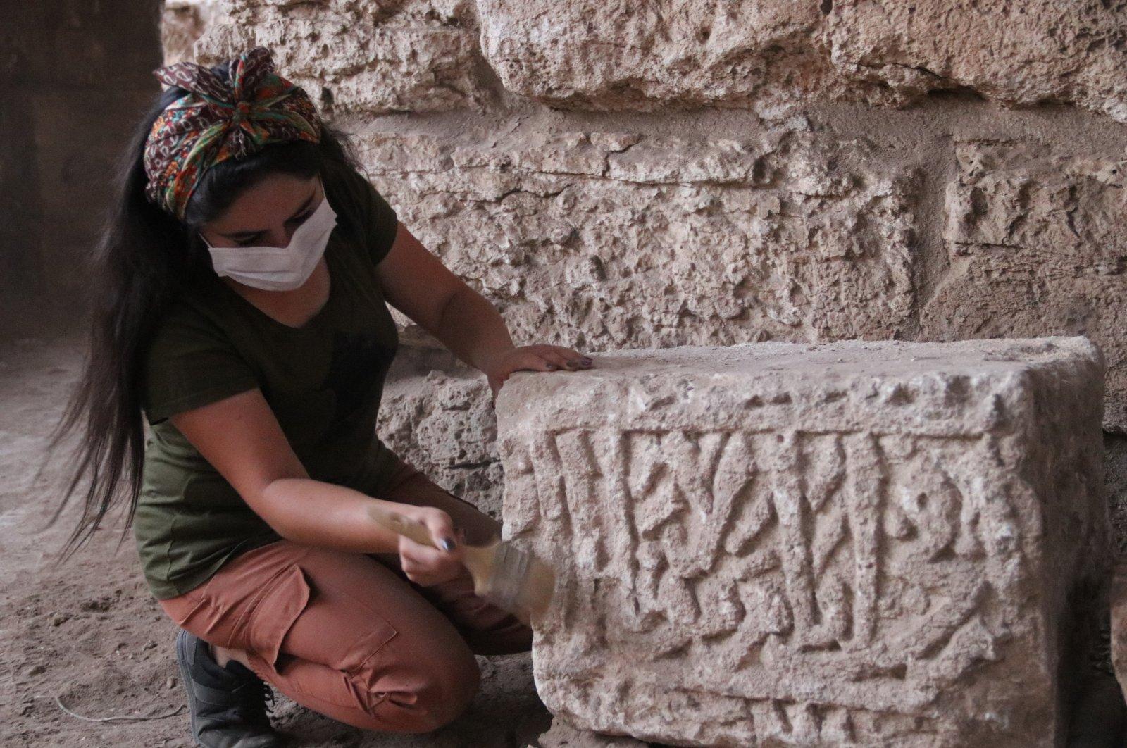 An archaeologist works on an inscription featuring Arabic writing on a basalt stone, Şanlıurfa, southeastern Turkey, Oct. 19, 2020. ( AA PHOTO)