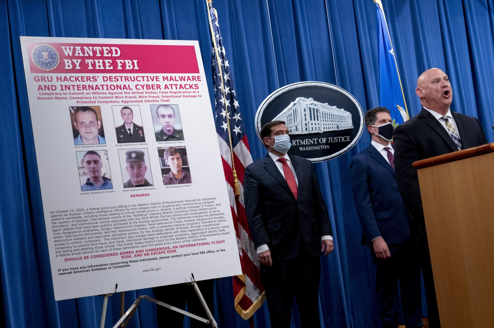 A poster showing six wanted Russian military intelligence officers is displayed as FBI Special Agent in Charge of the Pittsburgh field office Michael Christman (R) accompanied by Assistant Attorney General for the National Security Division John Demers (L) and FBI Deputy Director David Bowdich, (2nd R), speaks at a news conference at the Department of Justice, in Washington, DC, U.S., Oct. 19, 2020. (EPA Photo)