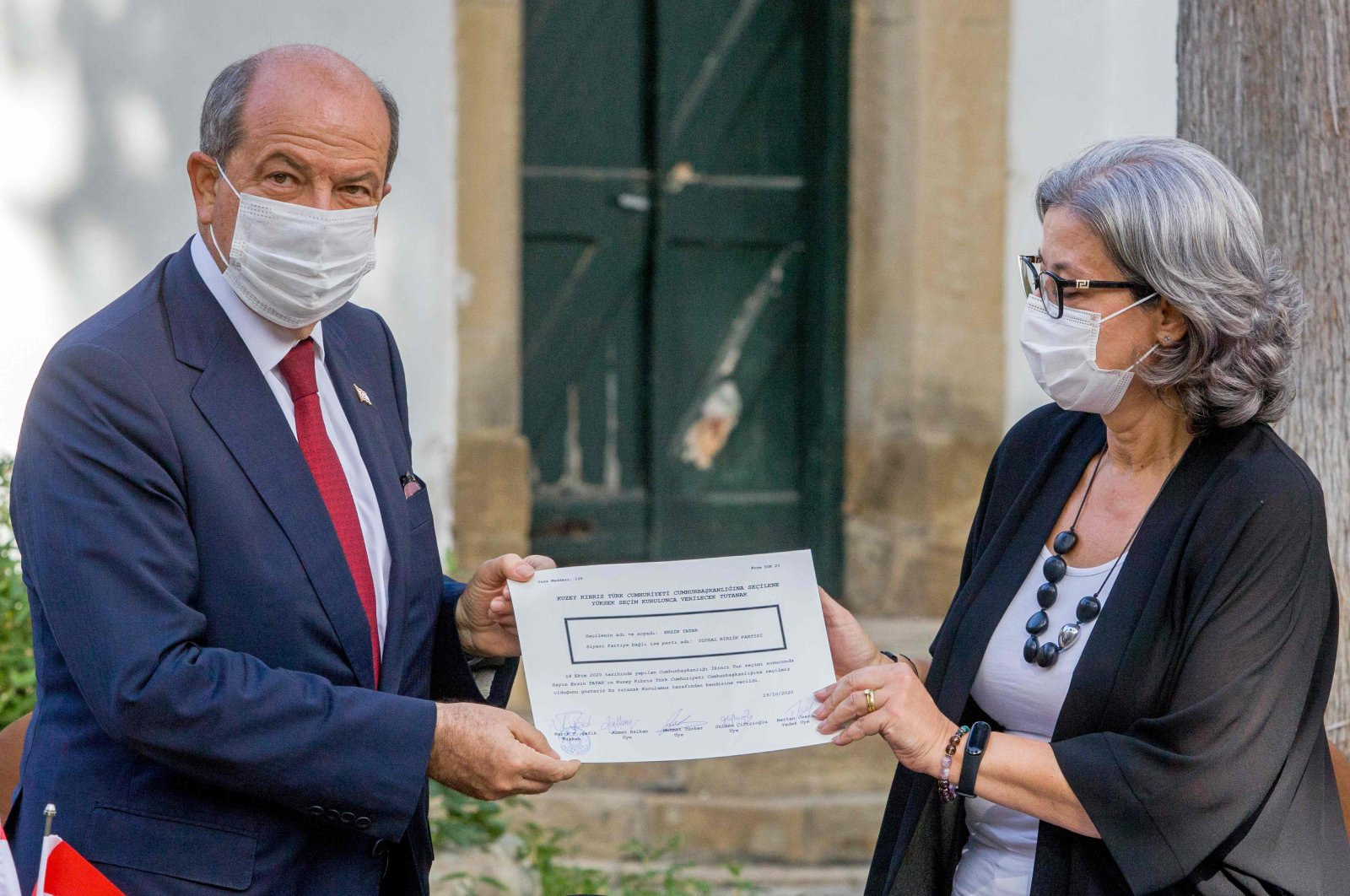 Newly elected Turkish Cypriot President Ersin Tatar (L) receives the certificate that accredits him as the winner of the presidential elections in the northern part of Nicosia (Lefkoşa), Turkish Republic of Northern Cyprus, Oct. 19, 2020. (AFP Photo)