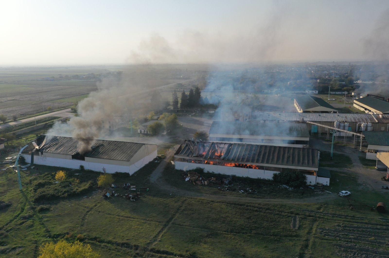 A cotton factory burns following Armenian artillery firedespite a cease-fire agreement between Baku and Yerevan, in a village in the Azerbaijani city of Tartar, Oct. 19, 2020. (AA Photo)